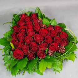 Heart of red roses with greens